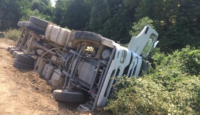 Yol inşaatında mıcır yüklü kamyon devrildi